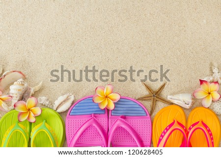 Flip Flops in the sand with shells and frangipani flowers. Summertime on beach concept. - stock photo