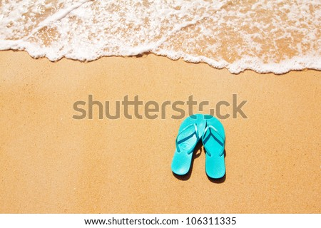 Flip flops on a sandy ocean beach - stock photo