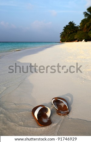 Flip-flops on a tropical beach at sunset - stock photo