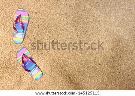 flip flops on beach sand. room for text. - stock photo