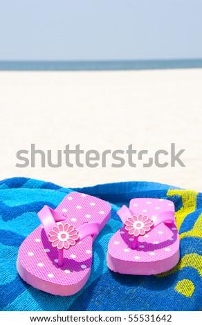 Flip flops on beach towel - stock photo