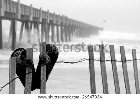 Flip flops on fence at beach by pier during tropical storm - stock photo
