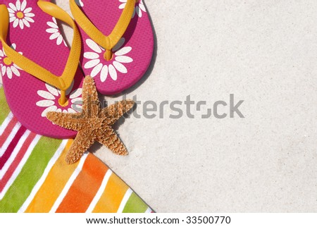 Flip flops on pretty beach towel by sand and starfish - stock photo