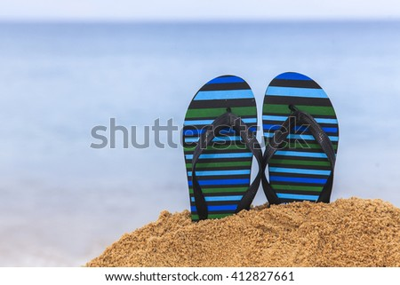 Flip flops on the sandy beach with blue sea