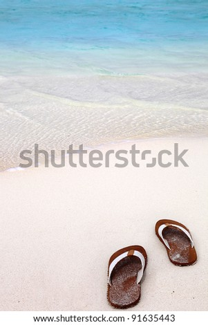 Flip flops on the white sands of a tropical beach - stock photo