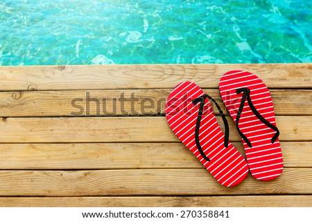Flip flops on wooden deck over water background - stock photo