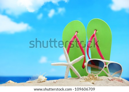Flip-flops,sunglasses with starfish on beach - stock photo