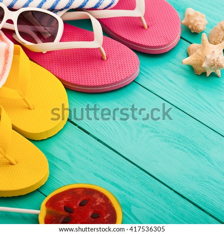 Flip flops, towels and candy on blue wooden table. Top view and selective focus  - stock photo