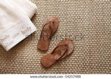Flip flops with fluffy towels on sea-grass rug - stock photo