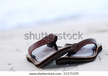Flipflops on a sandy ocean beach - summer vacation concept - stock photo