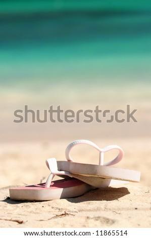 Flipflops on a sandy ocean beach - vacation concept - stock photo