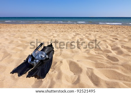 Flippers, mask and snorkel lying on sandy beach, horizontal orientation - stock photo