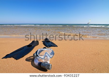 Flippers, mask and snorkel lying on wet sand, horizontal orientation