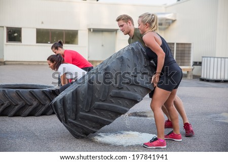 Flipping tractor tires as outdoor workout - stock photo