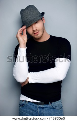 Flirtatious man wearing tilted hat against gray background - stock photo