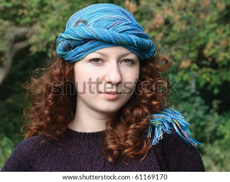 Flirtatious portrait of young woman with azure scarf on her head. The girl has red wavy long hair and a gentle white skin - stock photo