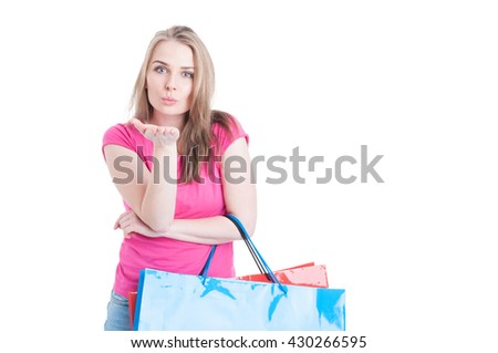 Flirting concept with attractive young woman sending a kiss while she is on shopping with copyspace isolated on white background - stock photo