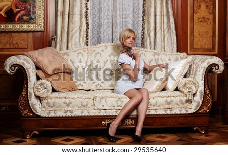Flirting maid sitting on a sofa in luxury hotel
