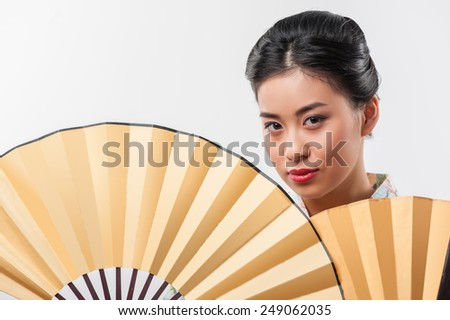 Flirty asian beauty. Closeup portrait of attractive Asian woman wearing Japanese kimono and posing with two traditional hand fans while standing against white background - stock photo
