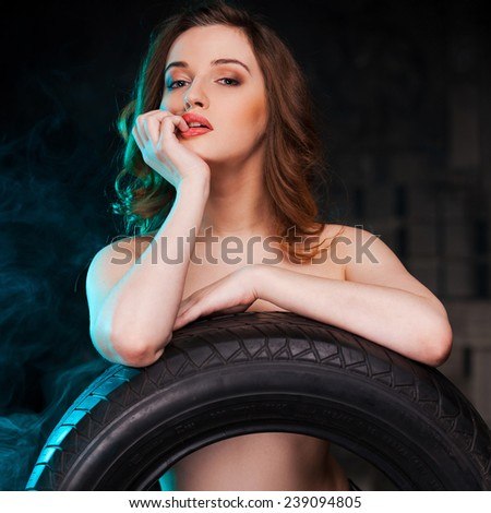 Flirty beauty. Beautiful young shirtless woman leaning at the car tire and holding finger on lips while standing in auto repair shop - stock photo