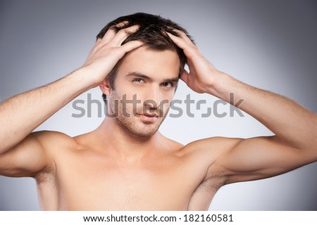 Flirty handsome. Portrait of handsome young beard man looking at camera and touching his hair with hands while standing isolated on grey background - stock photo
