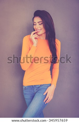 Flirty seductress. Beautiful young woman holding finger in mouth and smiling while standing against grey background - stock photo
