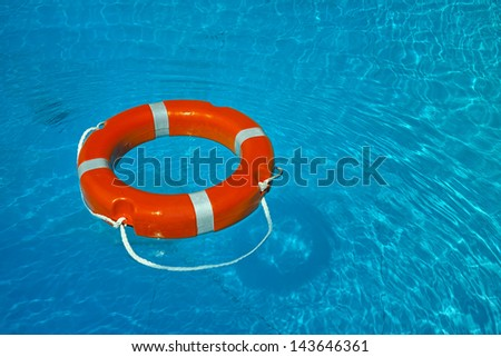float lifesaver on blue water - stock photo