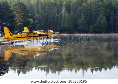 Float planes on the lake in the early morning mist - stock photo