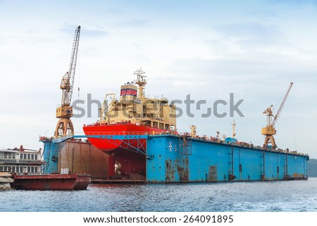 Floating blue dry dock with red tanker under repair inside, back view