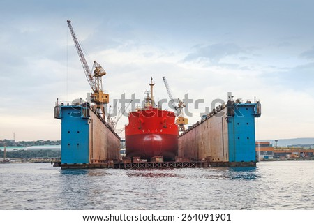 Floating blue dry dock with red tanker under repair inside, frontal view - stock photo