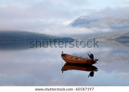 floating boat on mountain lake - stock photo