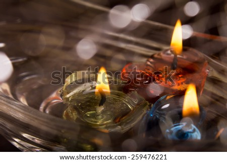floating burning candles on water with bokeh - stock photo