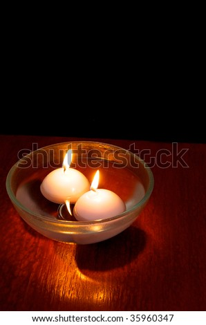 Floating candles on a wooden table with black background - stock photo
