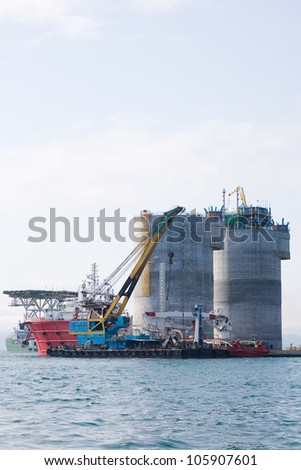 Floating crane and tugs at the base of the oil drilling platform. Port Nakhodka. Russia. Sea of Japan. - stock photo