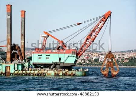 Floating crane dredging at Bosporus sea - stock photo