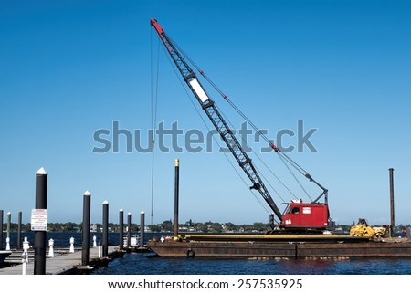 Floating crane working on the repair of a floating dock for the local marina - stock photo