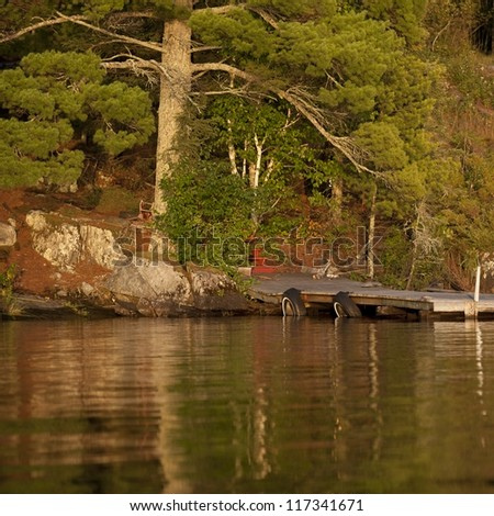 Floating dock at shoreline in Lake of the Woods, Ontario - stock photo