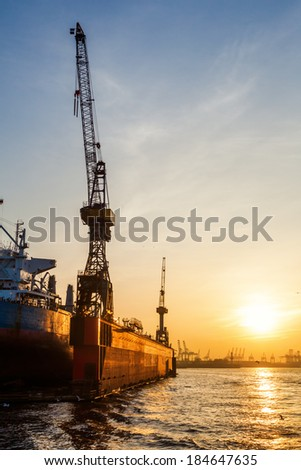 floating dock in the harbour of Hamburg, Germany, at sunset - stock photo