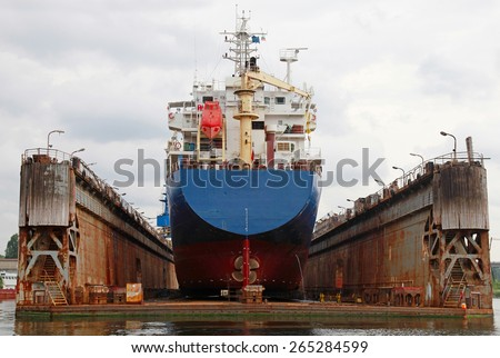 Floating dry dock with blue industrial tanker ship under repair inside, frontal view - stock photo