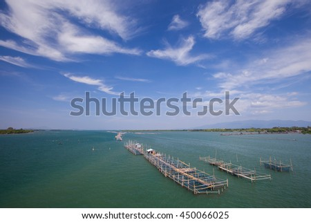Floating fish farm in sea and clear sky background - stock photo