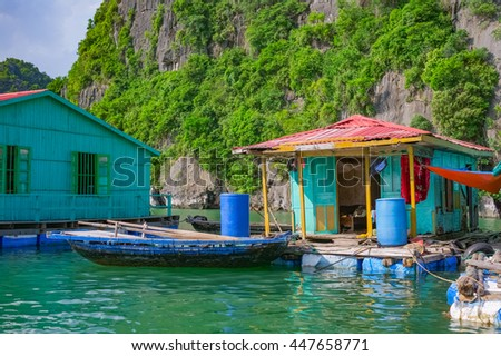 Floating fishing village near mountain islands in Halong Bay, Vietnam, Southeast Asia - stock photo