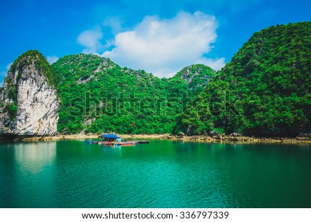 Floating house and rock island in Halong Bay, Vietnam, Southeast Asia - stock photo