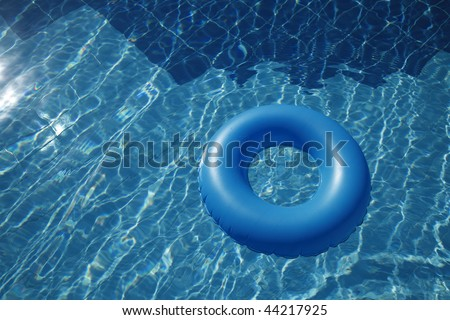 floating inner tube in a pool with waves reflecting in the summer sun - stock photo