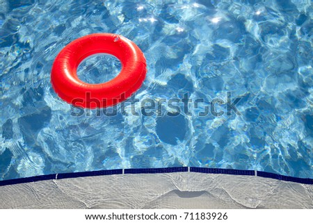 floating orange ring on edge of swimpool with waves reflecting in the summer sun - stock photo