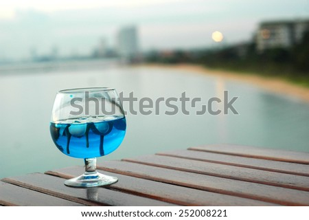Floating Plumeria in a glass with Sea background - stock photo