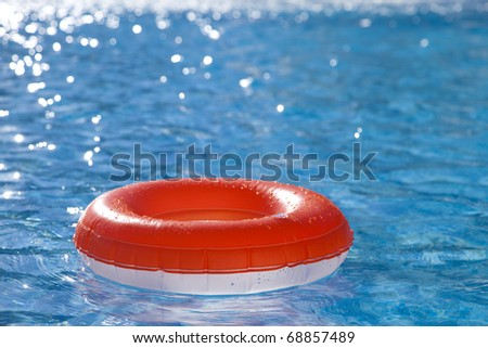 floating  ring on blue water swimpool with waves reflecting in the summer sun - stock photo
