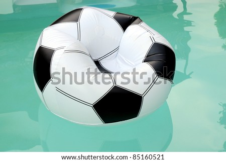 Floating rubber inflatable armchair resembling a soccer ball - stock photo