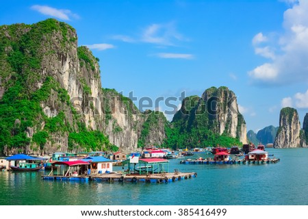 Floating village near rock islands in Halong Bay, Vietnam, Southeast Asia - stock photo