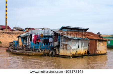 Floating village on Lake Tonle Sap in Cambodia with some houses made from boats - stock photo