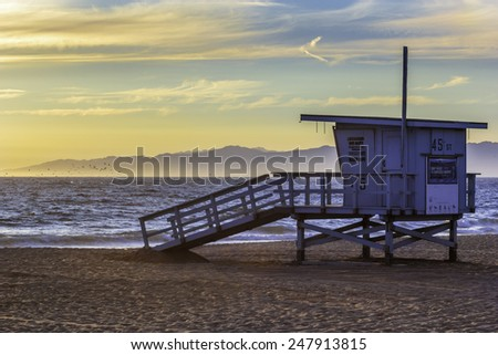 Flocks of seagulls and pelicans feed at sunset with a lifeguard tower looking and Malibu in the background on in Southern California - stock photo